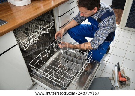 Portrait Of Male Technician Repairing Dishwasher In Kitchen - stock photo
