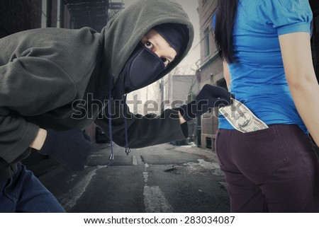 Portrait of male thief stole money from pocket of his victim at the street - stock photo
