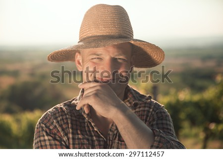 Portrait of male vintner with hat posing at vineyard - stock photo