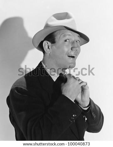 Portrait of man adjusting tie - stock photo