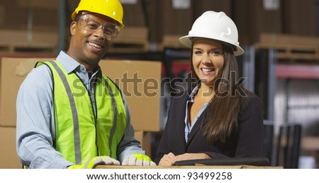 Portrait of man and woman in shipping warehouse - stock photo