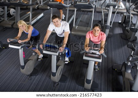 Portrait of man and women riding exercise bikes in health club - stock photo