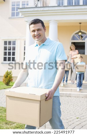 Portrait of man carrying cardboard box while moving house with family in background - stock photo