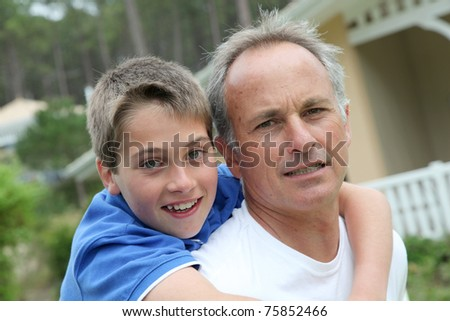 Portrait of man carrying child on his back - stock photo