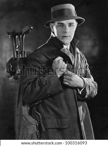 Portrait of man carrying golf clubs - stock photo