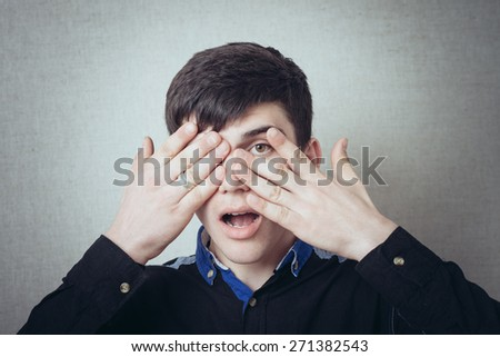 Portrait of man closed one eye with his hand - stock photo