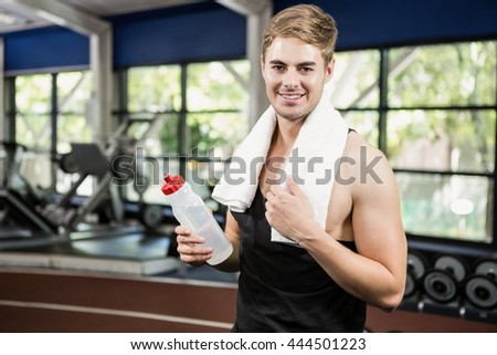 Portrait of man holding a water bottle at gym - stock photo