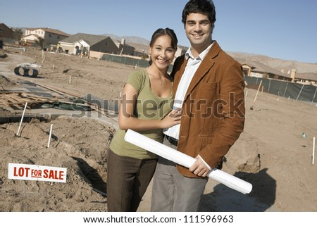 Portrait of man holding blueprint while standing with woman at a construction site - stock photo