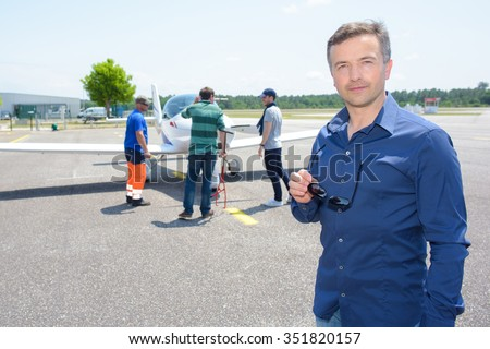 Portrait of man in airport, technicians checking his plane - stock photo
