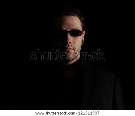 Portrait of man in black suit on black background - stock photo