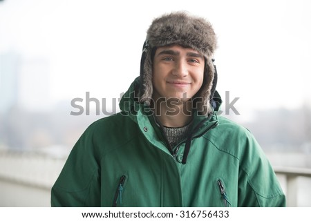 Portrait of man in winter wear smiling outdoors - stock photo