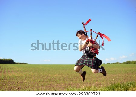 Portrait of man jumping high with pipes in Scottish traditional kilt on green outdoors copy space summer field - stock photo