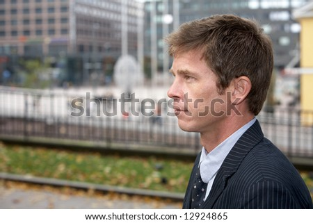 Portrait of man on city street, side profile - stock photo
