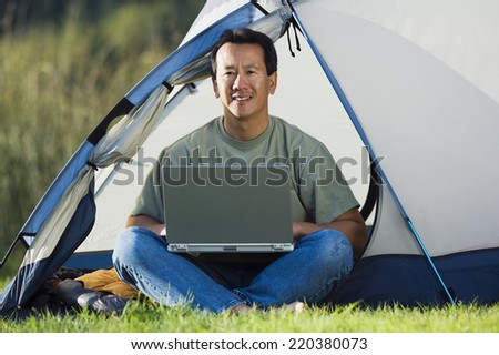 Portrait of man on laptop outside of tent - stock photo