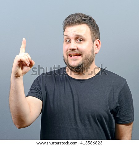 Portrait of man pointing up as a sign of having an idea against gray background - stock photo