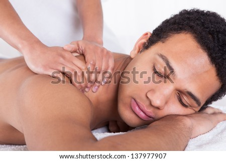 Portrait Of Man Receiving Massage Treatment From Female Hand - stock photo