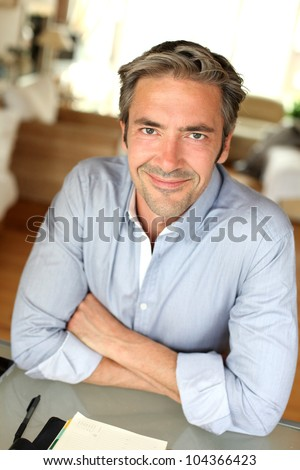 Portrait of man sitting at desk with arms crossed - stock photo