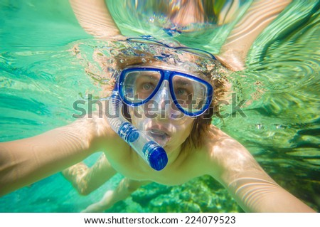 Portrait of man snorkeling in crystal clear laguna water on tropical island - stock photo