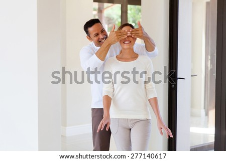 portrait of man surprise his wife with new house - stock photo