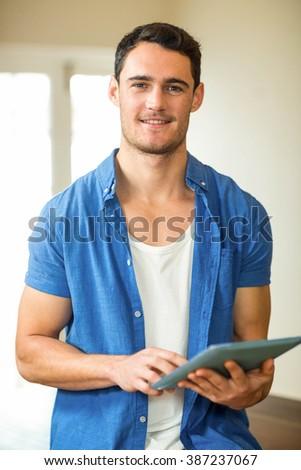 Portrait of man using digital tablet in kitchen - stock photo