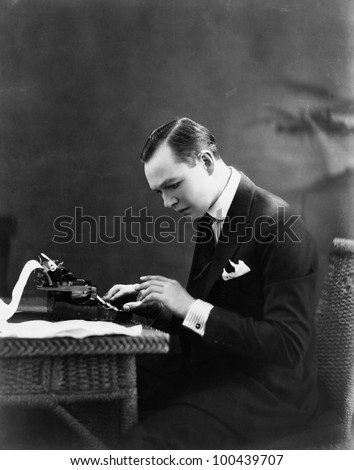 Portrait of man using typewriter - stock photo