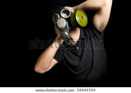 Portrait of man wearing a gas mask on black background - stock photo