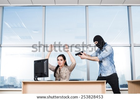 Portrait of man wearing black balaclava with gun looking at hostage scared business woman on blue sky window background Empty space for inscription Girl sit on table near pc computer Hands up - stock photo