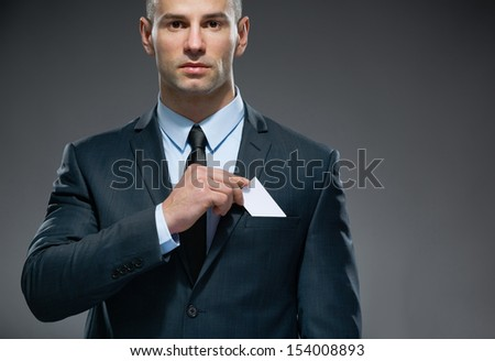 Portrait of man who pulls out white card from the pocket of business suit, copyspace - stock photo