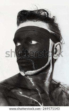 Portrait of man with black theatrical makeup on white background - stock photo