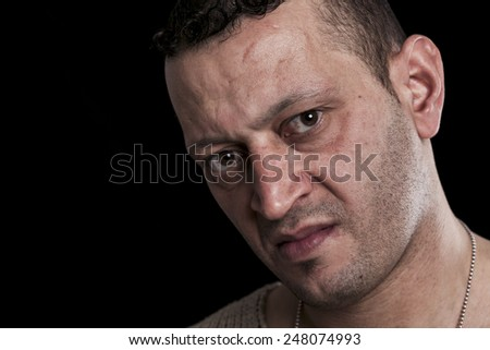 Portrait of man with frown looking at camera closeup - stock photo