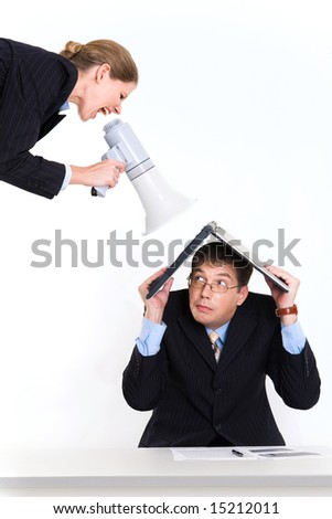Portrait of man with laptop on head scared by woman shouting through loud speaker - stock photo