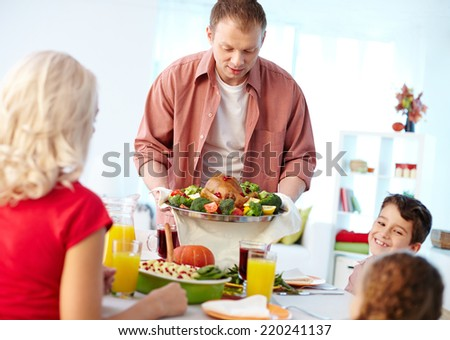Portrait of man with roasted turkey going to put it on table where his family sitting - stock photo