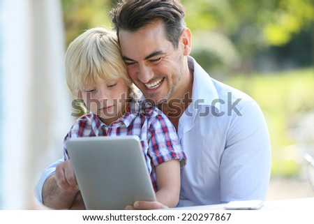 Portrait of man with son using digital tablet - stock photo