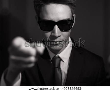 Portrait of man with sunglasses pointing his finger. - stock photo