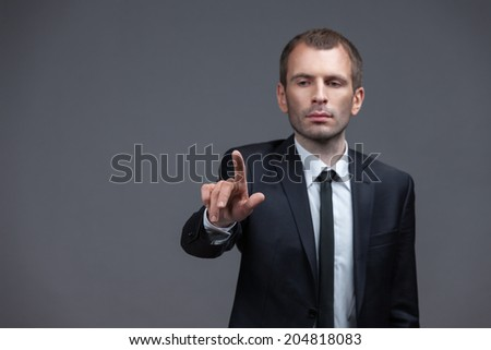 Portrait of manager pointing hand gestures, isolated on grey background. Concept of leadership and success - stock photo