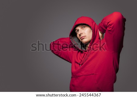 Portrait of Masculine Strong Tanned Caucasian Man in Red Hoody Jacket. Posing Against Gray Studio Backdrop. Horizontal Image Composition - stock photo
