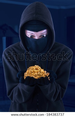 Portrait of masked man is holding stolen gold - stock photo