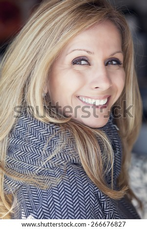 Portrait Of Mature Blond Woman Smiling At The Camera - stock photo