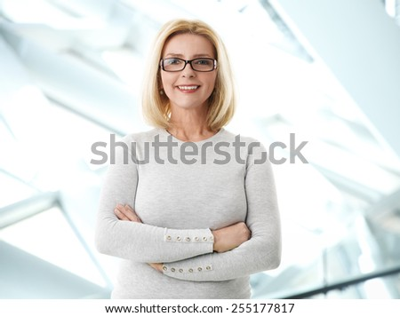 Portrait of mature business woman smile while standing at office.  - stock photo
