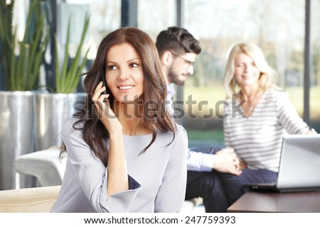 Portrait of mature business woman smiling during a telephone conversation while sitting at meeting. - stock photo