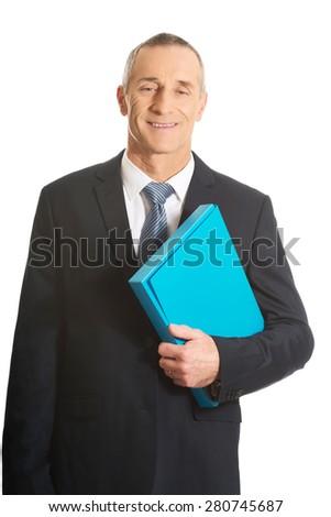 Portrait of mature businessman holding a binder. - stock photo