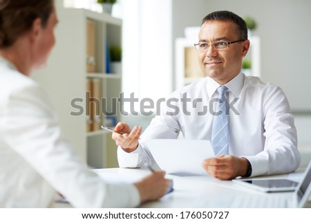 Portrait of mature businessman looking at his secretary while speaking to her - stock photo