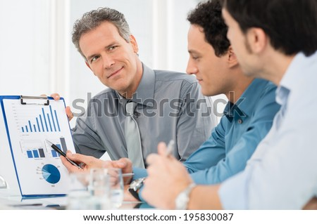 Portrait Of Mature Businessman Showing Annual Report Graph To His Colleague - stock photo