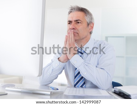 Portrait Of Mature Businessman Thinking At Desk In Office - stock photo