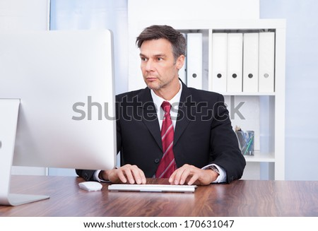 Portrait Of Mature Businessman Using Computer At Desk - stock photo