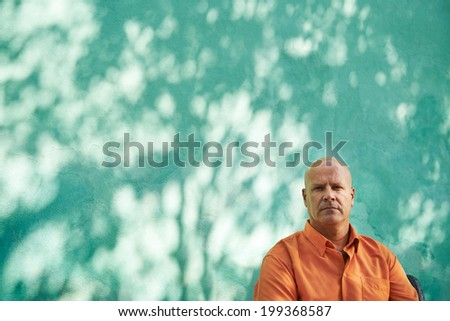 Portrait of mature caucasian man with orange shirt sitting in park and looking at camera with sad expression - stock photo