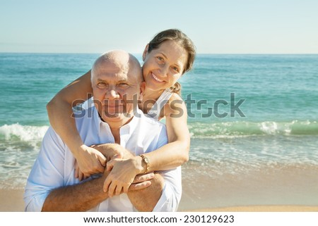 Portrait of mature couple against sea - stock photo