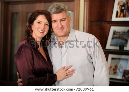 Portrait of mature couple embracing indoors - stock photo