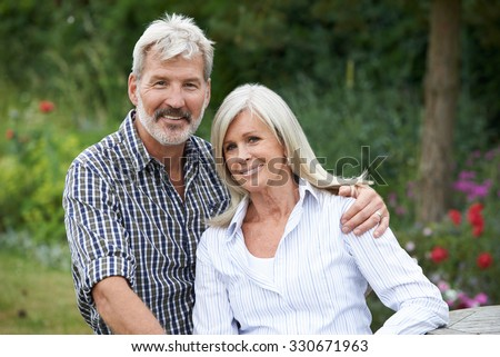 Portrait Of Mature Couple Relaxing In Garden Together - stock photo