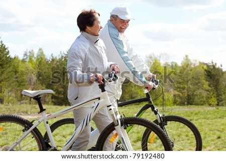 Portrait of mature couple with bicycles on weekend - stock photo